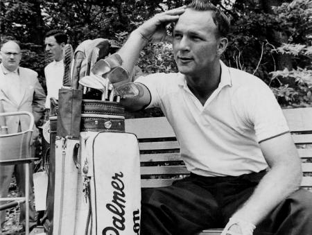 Arnold Palmer sentado em baco de madeira apoiado